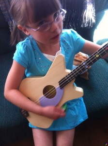 Little girl playing a Loog Guitar